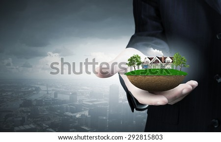 Close up of hand presenting model of green countryside life
