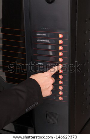 Close-up of hand pressing button of vending machine for coffee - stock photo