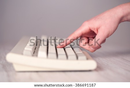 Close up of hand pressing keyboard buttons on desk