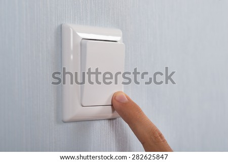 Close-up Of Hand Pressing White Switch On Wall