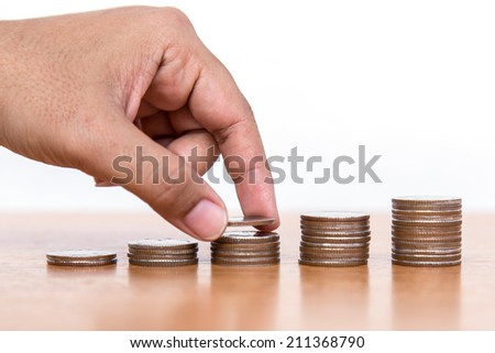 Close up of hand put coins to Stack Of Coins