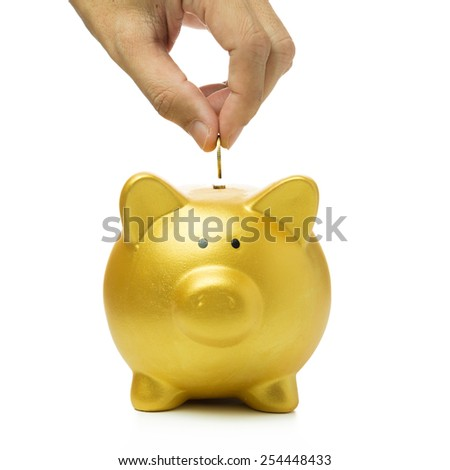 Close up of hand putting coin into golden piggy bank