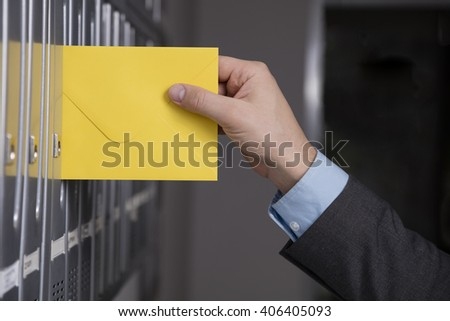 Close up of hand putting the yellow letter into the mailbox