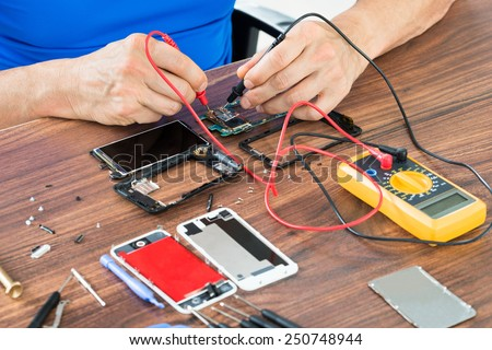 Close-up Of Hand Repairing Cellphone With Multimeter At The Wooden Table - stock photo