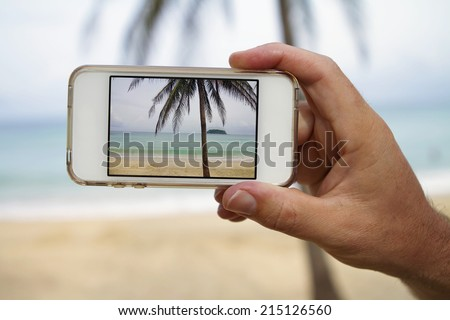 Close up of hand taking a photograph of palm tree with mobile phone screen - stock photo