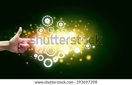 Close up of hand touching icon of gears on media screen - stock photo
