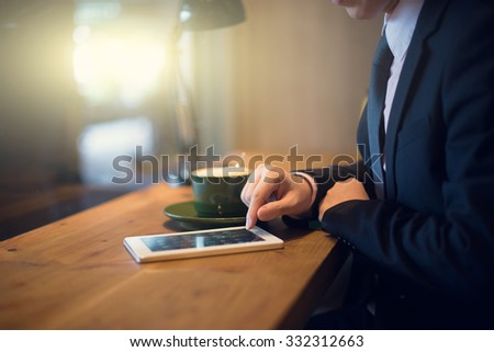 close up of hand using tablet computer at cafe