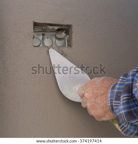 Close-up of hand using trowel to finish wet concrete wall at construction site - stock photo