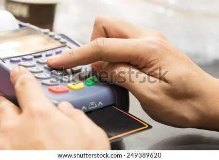 Close Up Of Hand With Credit Card Swipe Through Terminal For Sale In Store - stock photo