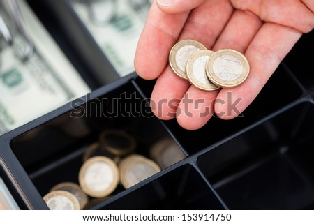 Close-up Of Hand With Euro Coins  Over Container - stock photo
