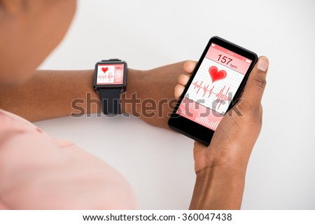 Close-up Of Hand With Mobile And Smartwatch Showing Heartbeat Rate - stock photo