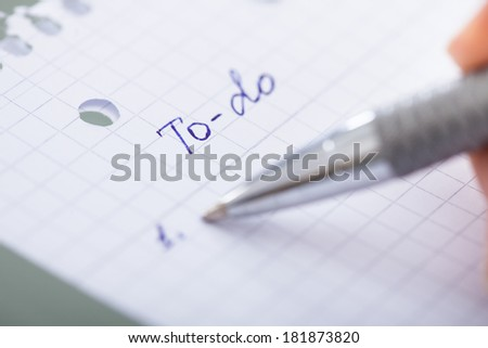 Close-up Of Hand With Pen Filling Out To Do List - stock photo