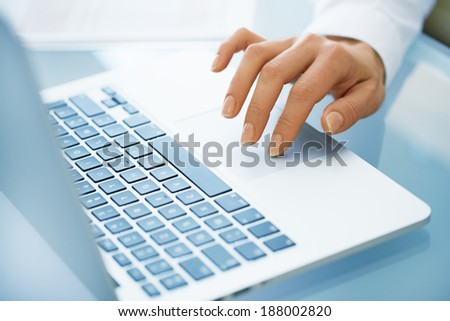 Close-up of hand woman using a laptop computer on desk  - stock photo