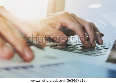 close up of hand working with business documents on office table with laptop computer and digital graph business diagram - stock photo
