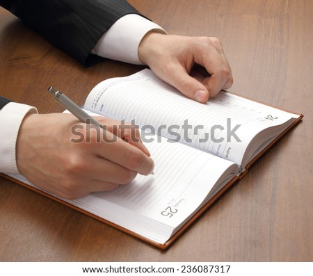 Close up of hand writing and notepad on a table