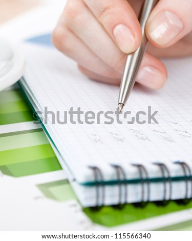 Close up of hand writing in the writing pad lying on the diagrams - stock photo