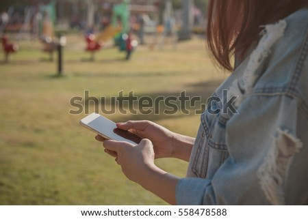 Close up of  hand  young woman holding mobile smartphone in the park, vintage style.