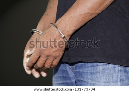 Close up of handcuffed hands on a black background - stock photo