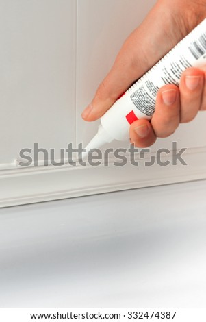 Close up of hands caulking bath tube with white silicone glue