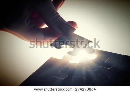 Close up of hands connecting puzzle element and making jigsaw complete - stock photo