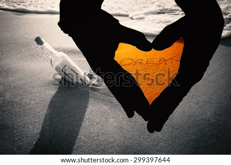 Close up of hands forming heart against inscription dream on sand - stock photo