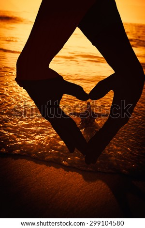 Close up of hands forming heart against starfish on the sand - stock photo