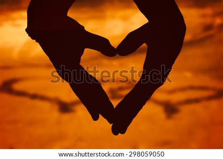 Close up of hands forming heart against two hearts drawn in the sand - stock photo