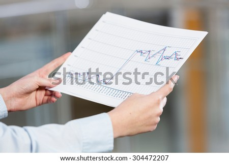 Close up of hands holding paper with graphs and diagrams