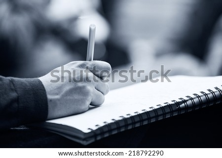 Close-up of Hands holding pens and making notes at the conference. Monochromatic - stock photo