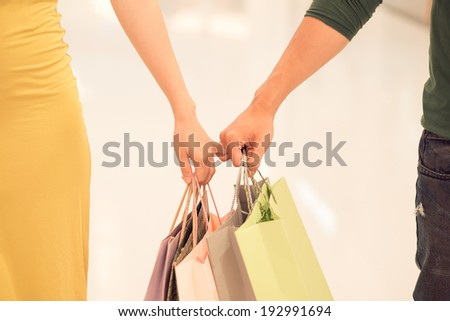 Close-up of hands holding shopping bags - stock photo