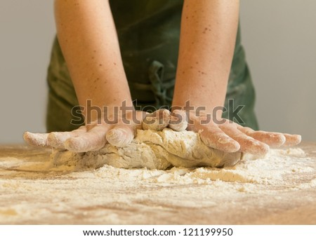 Close up of hands kneading dough - stock photo