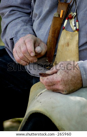 Close-up of hands making flint arrows.