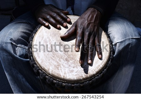 Close up of hands of a black man playing a drum - stock photo