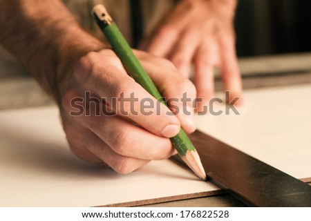 close-up of hands of a joinery while measuring and marking the wood that will work - stock photo