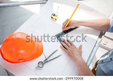 Close up of hands of architect drawing sketches of new building with a ruler and pencil. He is sitting at the table. There are his helmet and compass on the blueprint - stock photo