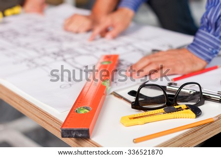 Close up of hands of architects discussing a new project. They are standing near the blueprint. The man is pointing finger at a sketch - stock photo