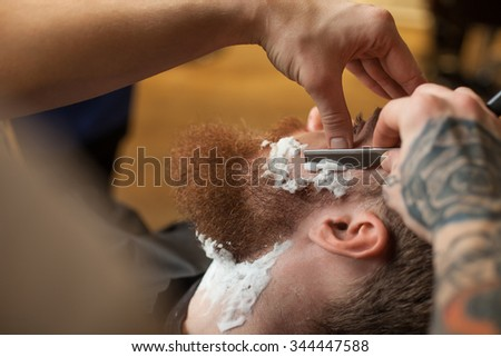 Close up of hands of barber shaving beard of the customer. He is touching a blade to human face. The man is sitting in chair with concentration - stock photo