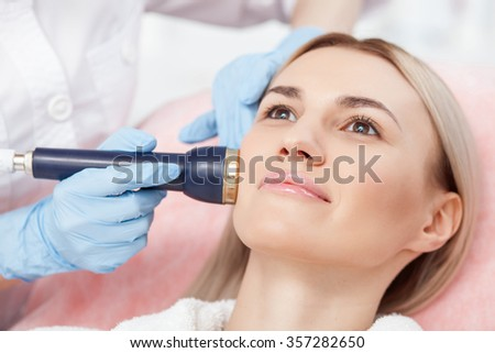 Close up of hands of beautician making cavitation treatment on human face with the equipment. The woman is lying and gently smiling - stock photo