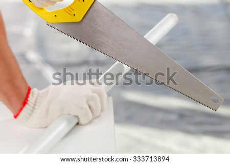 Close up of hands of builder sawing a stick. The man is holding metal saw - stock photo
