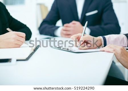 Close-up of hands of business meeting. Female hands holding a silver pen closeup. Business woman making notes at office workplace.