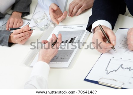 Close-up of hands of business people and graphics