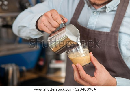 Close up of hands of cafeteria worker making late. The man is holding a cup and pouring milk into it carefully - stock photo
