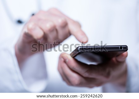 Close-up of hands of doctor using phone in hospital - stock photo