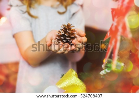 Close up of hands of little girl holding on palms pine cone painted in bronze color. Child ready to decorate Christmas tree. Horizontal color photo.