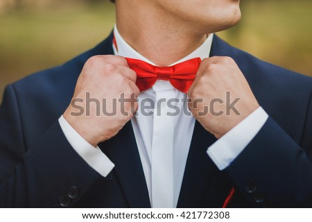 Close up of hands of man correcting red bowtie. Man wears blue suit, white shirt and red bowtie. Groom or graduate. Formal style of clothes. - stock photo