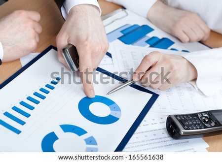 Close up of hands of managers discussing diagram and sitting at the table with heap of documents - stock photo