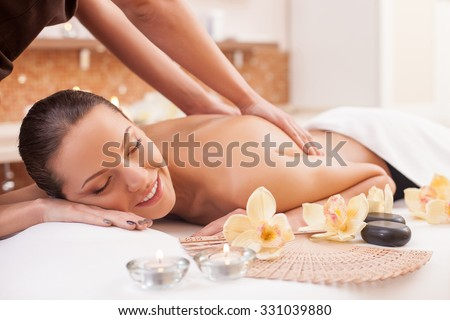 Close up of hands of masseuse massaging back of young lady. The beautiful woman is lying and relaxing. She is smiling. Her eyes are closed with relaxation - stock photo