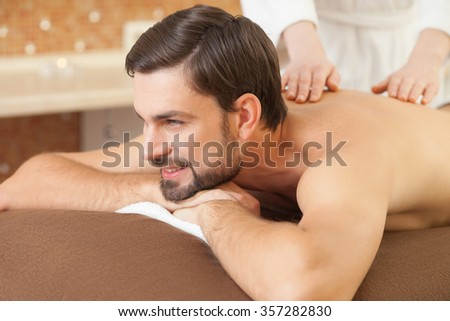 Close up of hands of masseuse massaging male back carefully. The man is looking forward and smiling. He is lying at spa - stock photo