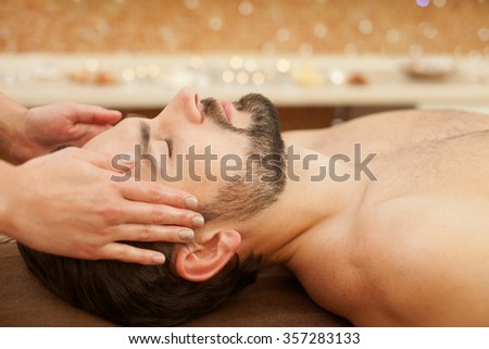 Close up of hands of masseuse massaging male head. The man is lying at spa. His eyes are closed with pleasure