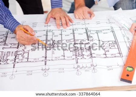 Close up of hands of professional architects discussing the project. They are standing near the blueprint. The man is holding a pencil and pointing it at a sketch of building - stock photo